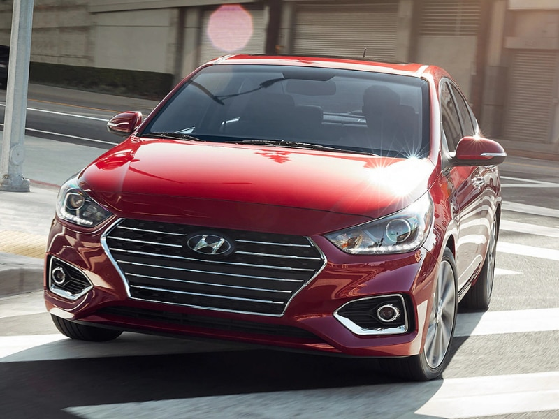 2020 Hyundai Accent red color in motion turning city corner sun reflection hood
