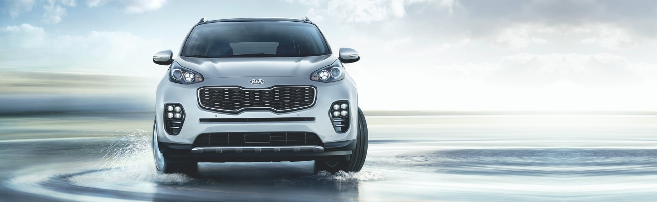 Front angle of a silver 2019 Kia Sportage driving through a field of sitting water splashing up by the spinning tires