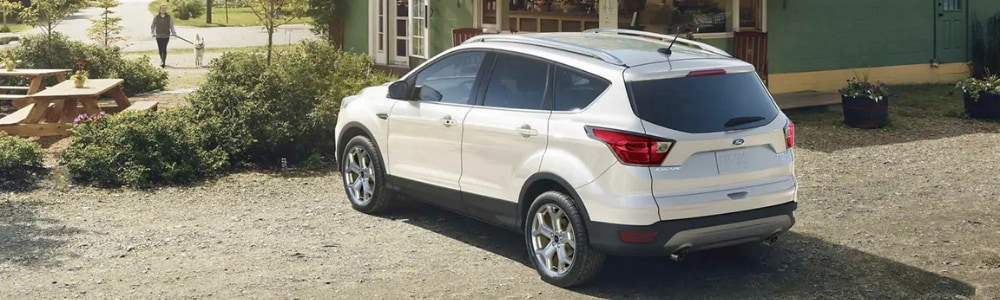 Rear angle of the driver side on a white 2019 Ford Escape parked outside of a cafe with a woman walking her dog through the garden