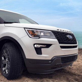 The front passenger side of a white 2019 Ford Explorer parked with the wheels turned on a sandy beach and crystal clear ocean water in the background