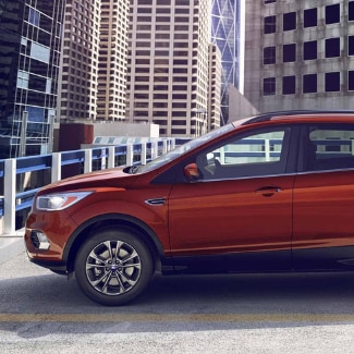 The driver side of an orange 2019 Ford Escape parked on the top floor of a parking garage in a big city with tall skyscrapers featured in the background