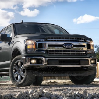 A close up view from the ground of a black 2019 Ford f-150 parked in a construction site with rocks in the foreground and a partly cloudy blue sky in the background