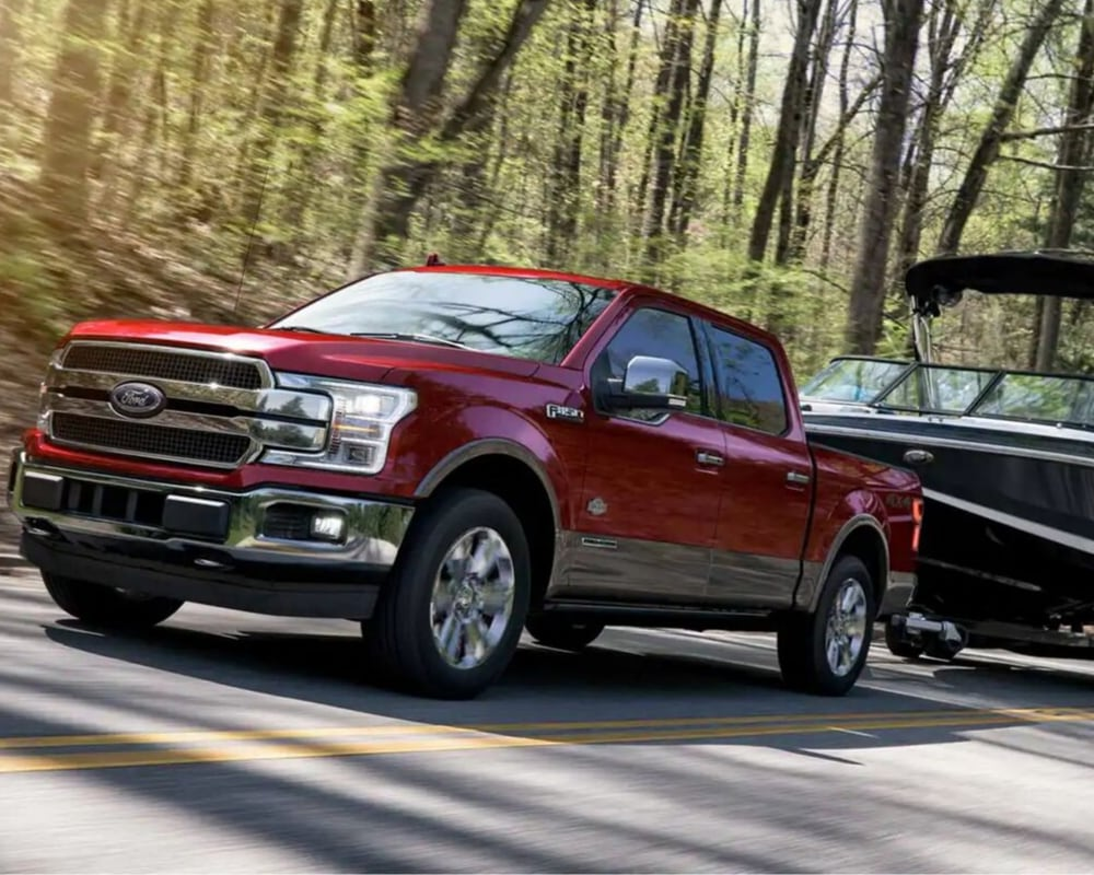 Ruby Red 2019 Ford F-150 towing a large boat down a highway