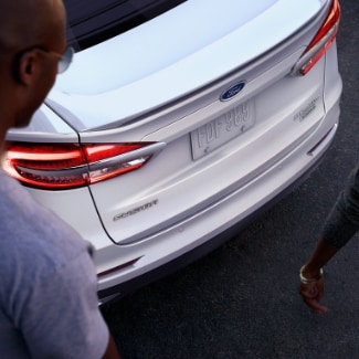 A birds eye view of two people walking by and admiring the back of a white 2019 Ford Fusion