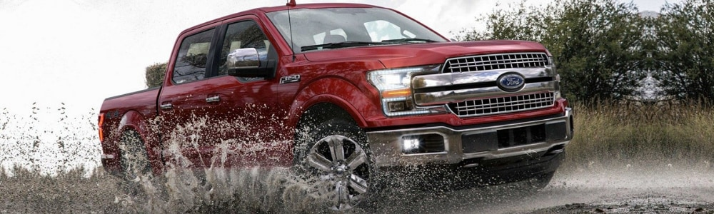 Angle of the passenger side of a ruby red 2019 Ford F-150 driving through a puddle with muddy water splashing onto the side of the Ford truck on a cloudy day