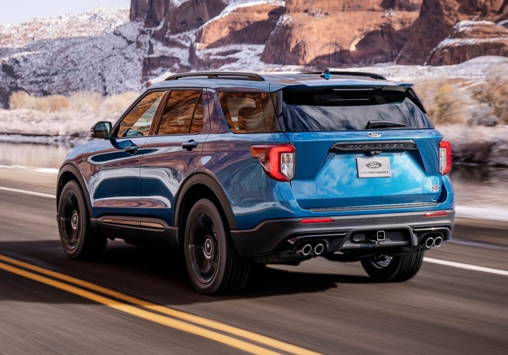 Rear exterior view of the 2020 Ford Explorer ST in Ford performance blue speeding down the open road