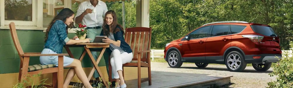 Three friends sitting at a round wooden table outside a country cafe enjoying their meals as a brand new red 2019 Ford Escape awaits them in the parking spot