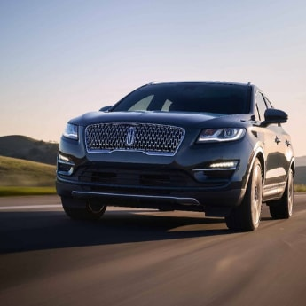 The front angle of a blue 2019 Lincoln MKC with tires spinning as it speeds down an open country road with green hills in the background