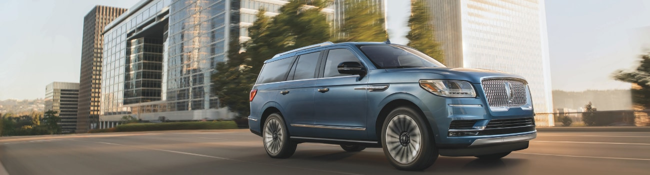 View of the passenger side of a light blue 2019 Lincoln Navigator driving down a highway with blurred images of trees and tall city buildings in the background