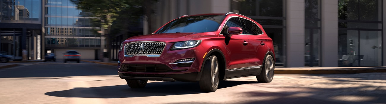In-motion shot of a red 2019 Lincoln MKC making a turn around a street corner in Colorado Springs