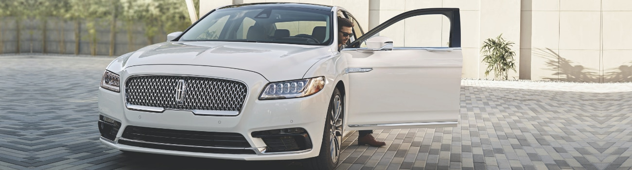 Front angle of a white 2019 Lincoln Continental with the driver side door open as the driver gets out of the new Lincoln car parked in his driveway