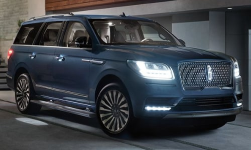 2020 Lincoln Navigator blue parked under shaded driveway awning headlights on
