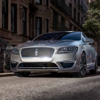 A look at the front of a silver 2019 Lincoln MKZ with a slight view of the undercarriage parked in front of an upscale apartment building in the city