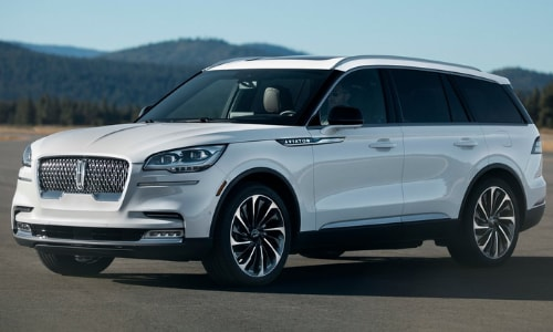 2020 Lincoln Aviator Black Label white driver side exterior open asphalt lot forest backdrop