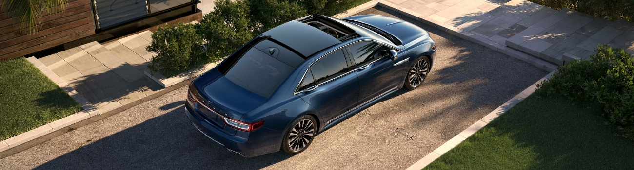 Aerial view of a dark blue 2019 Lincoln Continental as the moonroof opens parked in the driveway of a classy modern home