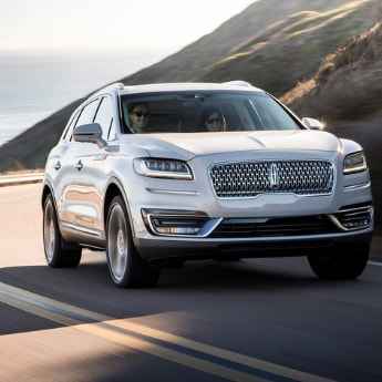 A front side shot of a white 2019 Lincoln Nautilus driving around a curvy road edging the small mountains with a beautiful view of the ocean on the left