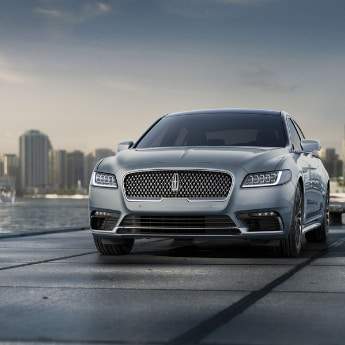 A view of the front of a dark silver 2019 Lincoln Continental parked at the end of a concrete pier overlooking a bay of water with sailboats and a big city on the distant horizon