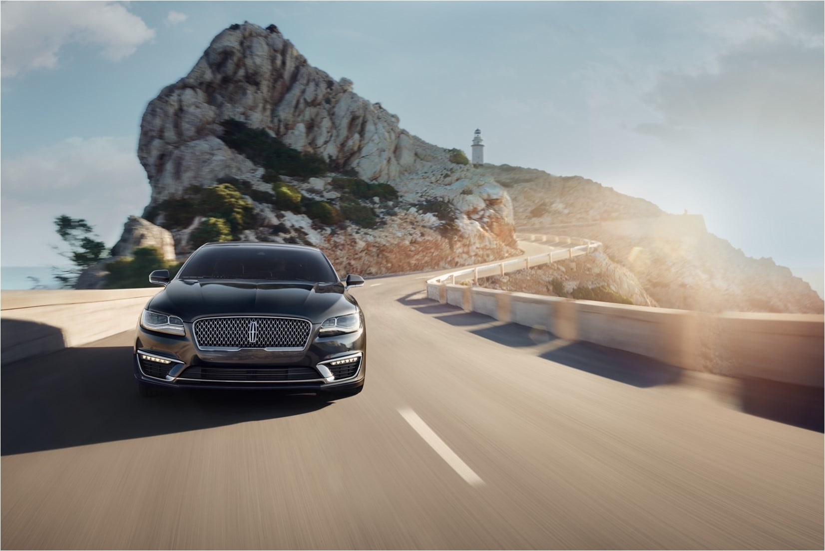 A 2020 Lincoln MKZ driving on a scenic road with ocean rocks and a lighthouse in the distance