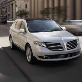 An off-white 2019 Lincoln MKT driving down a busy city street in front of the city municipal building with blurred images of cars as they pass by in the background