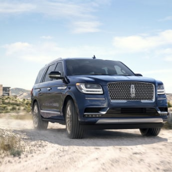 The front passenger side angle of a blue 2019 Lincoln Navigator making a turn around a sandy dirt road with a desert scenery in the background