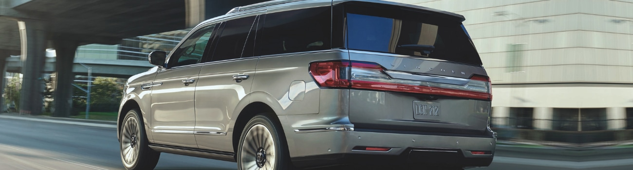 Rear driver side angle of an ingot silver 2019 Lincoln Navigator driver down a city street under an overpass
