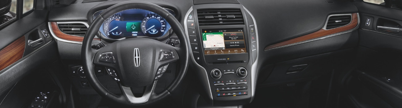 Interior view of a 2019 Lincoln MKC showing the luxurious dashboard, touch screen system and sleek dark wooden trim