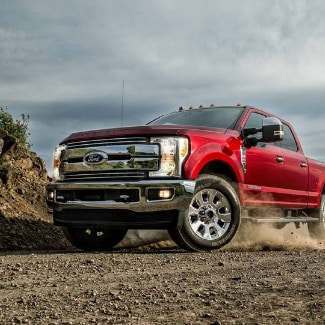 A red 2019 Ford Super Duty turning around the curve of a dirt path with dust flying from the tires under the truck on a partly cloudy day