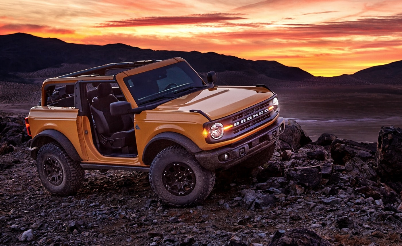 A cyber orange 2021 Ford Bronco 2-door with doors and roof removed sitting in front of an orange sunset sky behind a dark mountain range