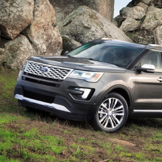 A dark silver 2019 Ford Explorer driving up a grassy hill around some big rocky boulders sitting in the background