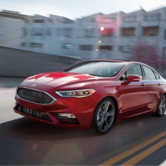 A red 2019 Ford Fusion driving fast down a city highway with the sun glaring off the hood and a view of blurred apartment buildings in the background