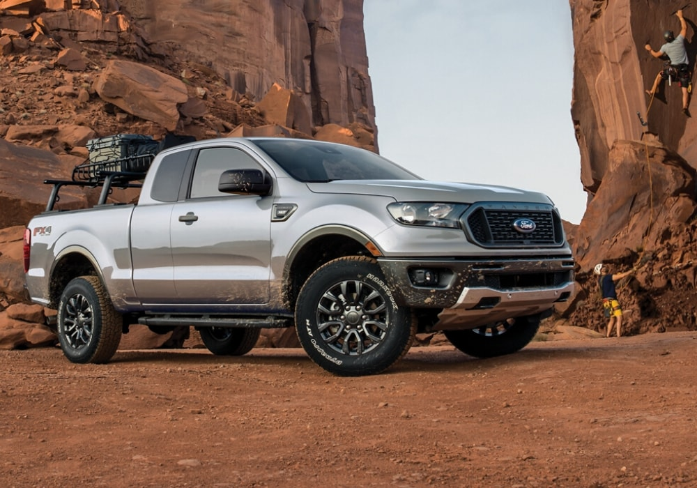 2020 Ford Ranger silver color parked by red clay mountains mountain climbers