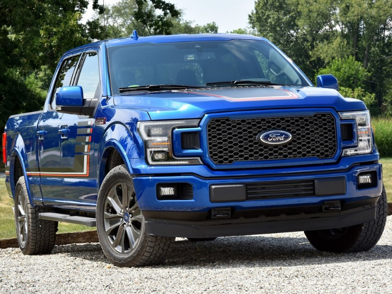 Exterior of a blue 2019 Ford F-150 parked on a gravel road beside a forest