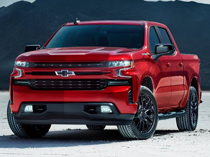 Exterior view of a 2019 Chevy Silverado parked in a sandy field in front of mountains