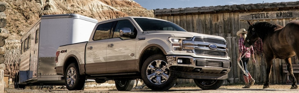 Front passenger side angle of an off white 2019 Ford F-150 pulling a horse trailer parked outside of a barn with a woman walking a horse by the Ford truck