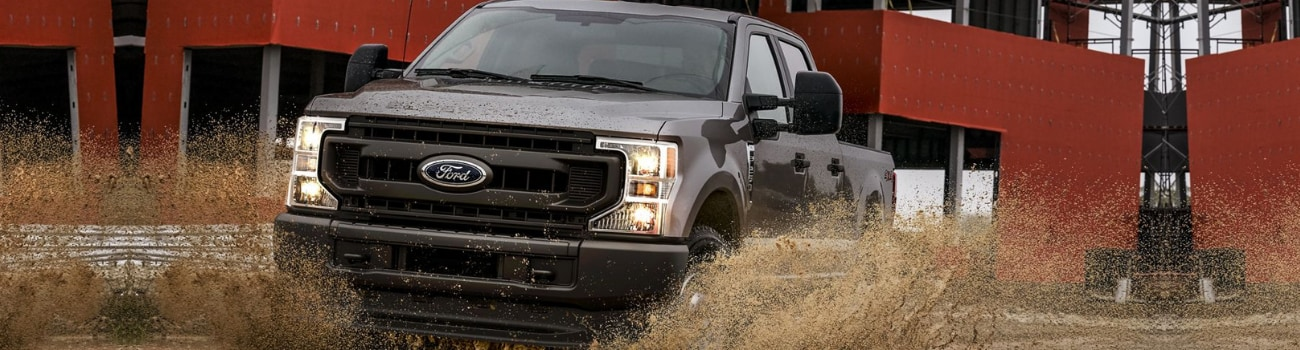 2020 Ford Super Duty F-250 plowing through a muddy puddle construction site
