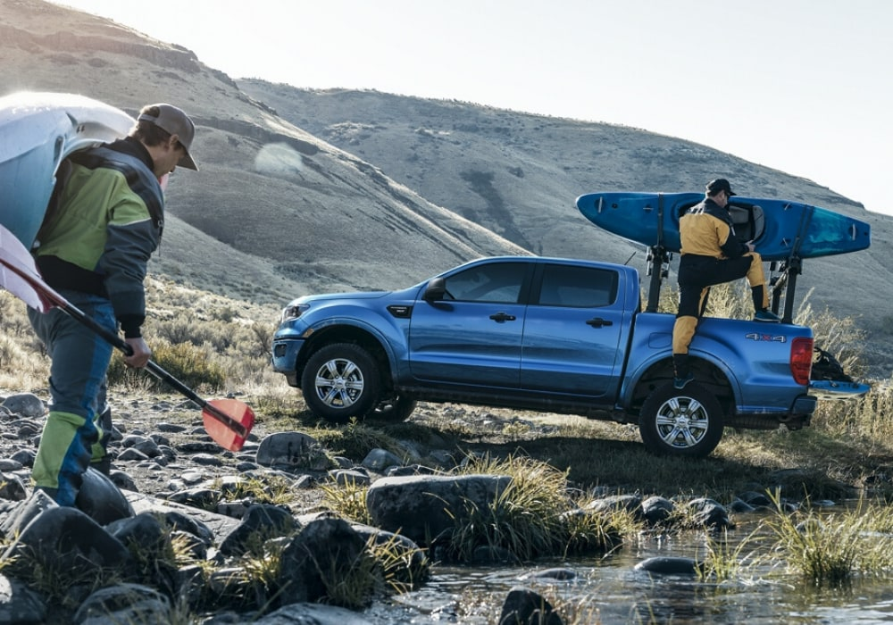 2020 Ford Ranger blue exterior color parked by a river loading kayaks and paddles