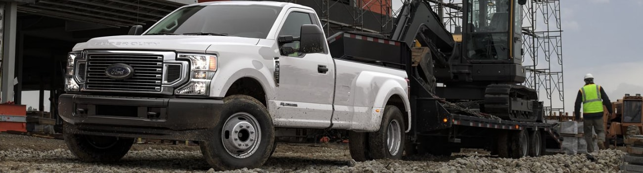 2020 Ford Super Duty in white towing heavy large construction equipment