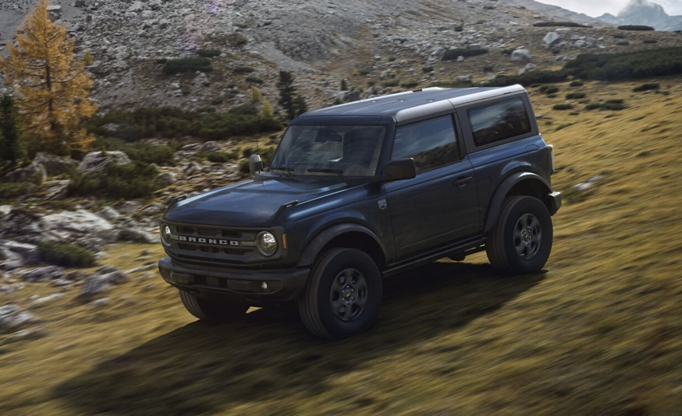 New 2021 Ford Bronco in Antimatter Blue speeding down a rocky, grassy off-road hill