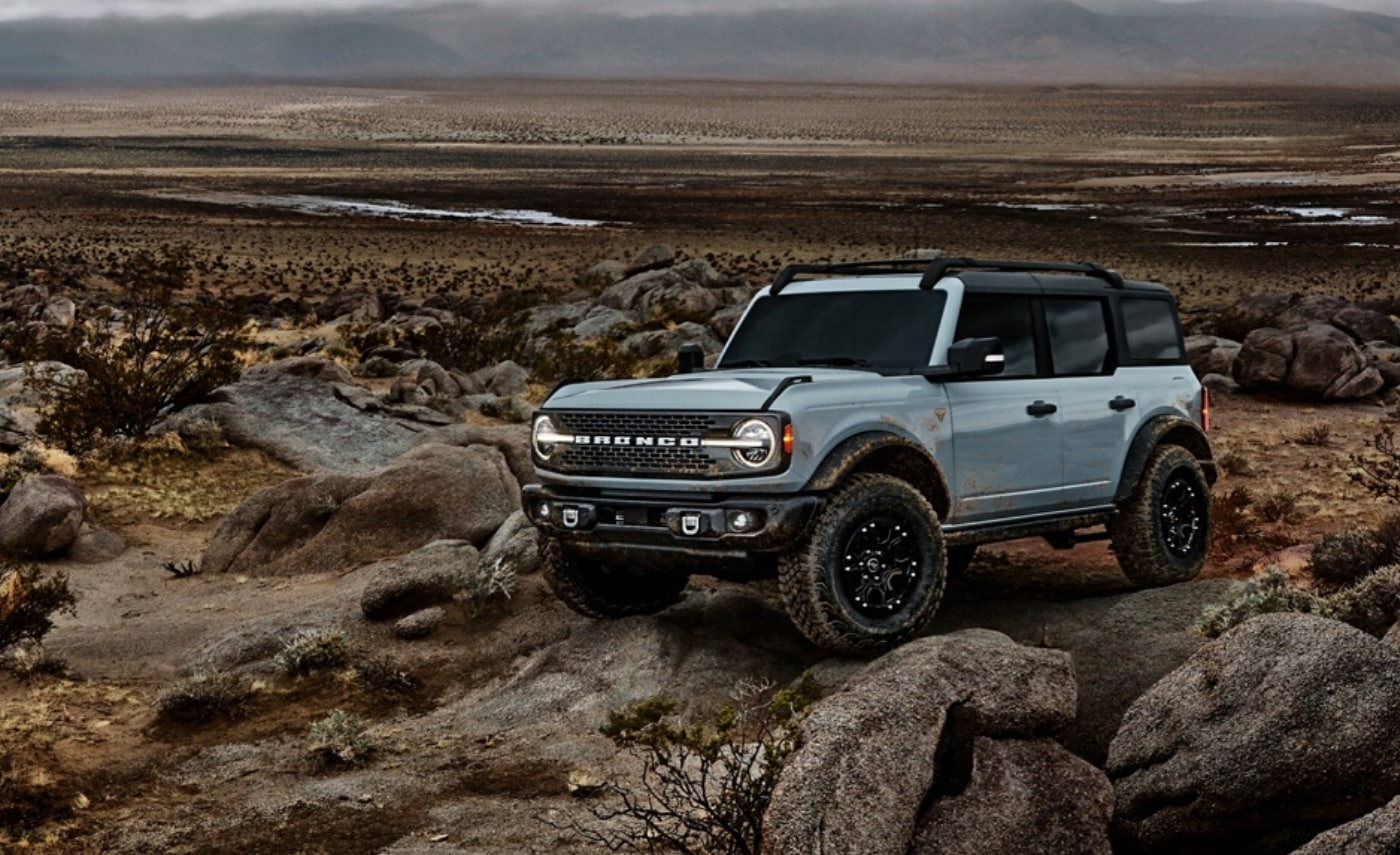 New 2021 Ford Bronco 4-Door in Cactus Gray color climbing over some big rocks in the desert