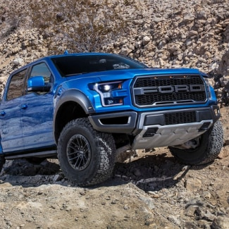 A blue 2019 Ford F-150 Raptor driving up a rocky cliff with a rocky desert scenery in the background