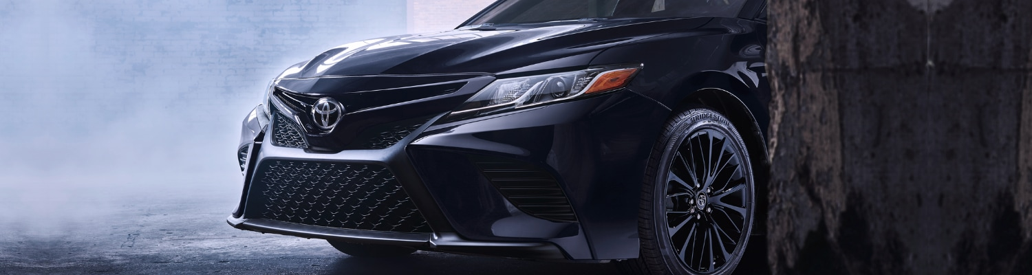 2019 Toyota Camry black color zoomed in angle front grille hazy garage scene drifting smoke