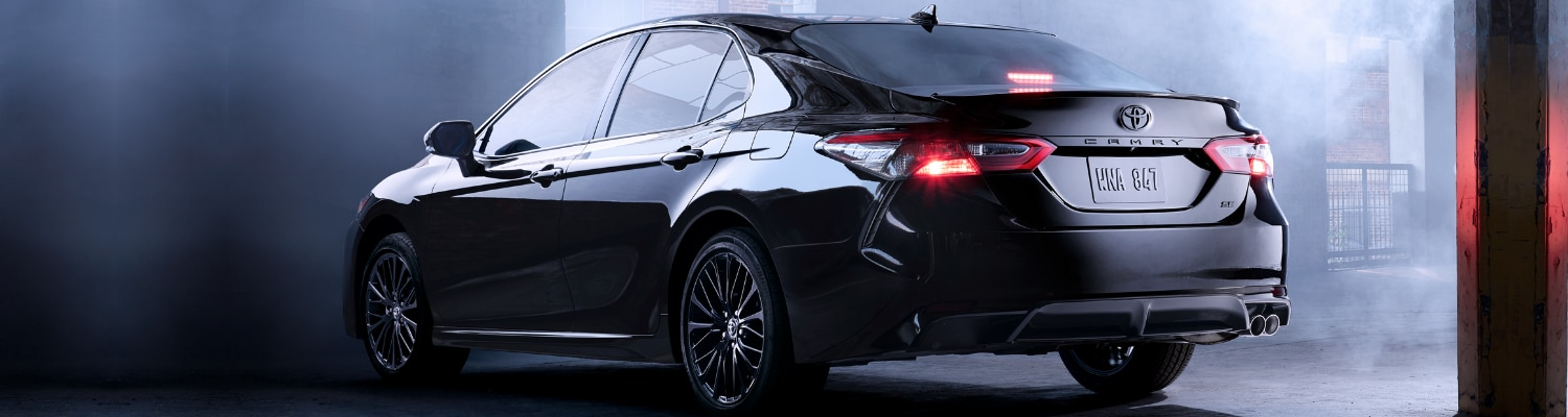 2019 Toyota Camry rear driver side view parked in a smokey hazy dark garage