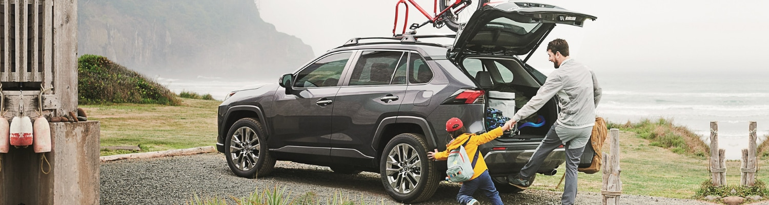 Driver side view of a dark grey 2019 Toyota RAV4 parked in a gravel driveway with a man and his son unloading baggage from the back