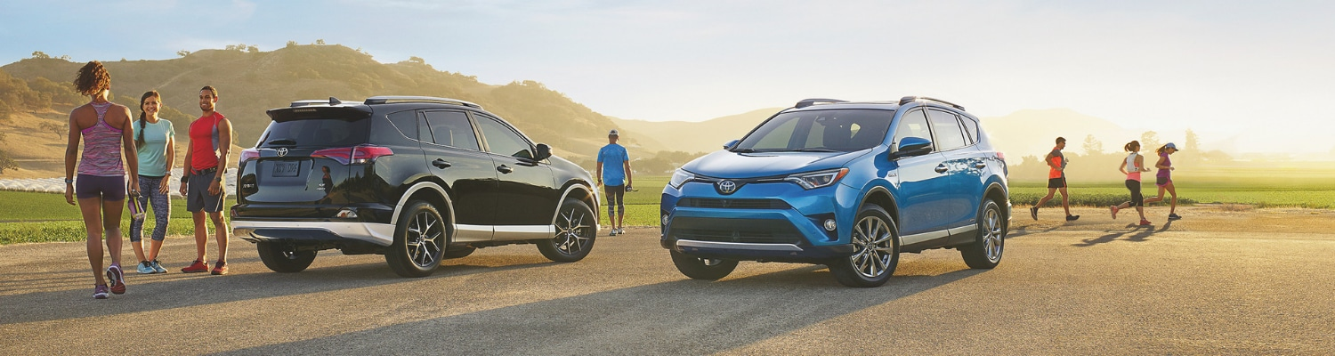 Lifestyle photograph of two 2019 Toyota Rav4 models parked on a dirt opening as the sun rises in the background with drivers and passengers getting ready to exercise