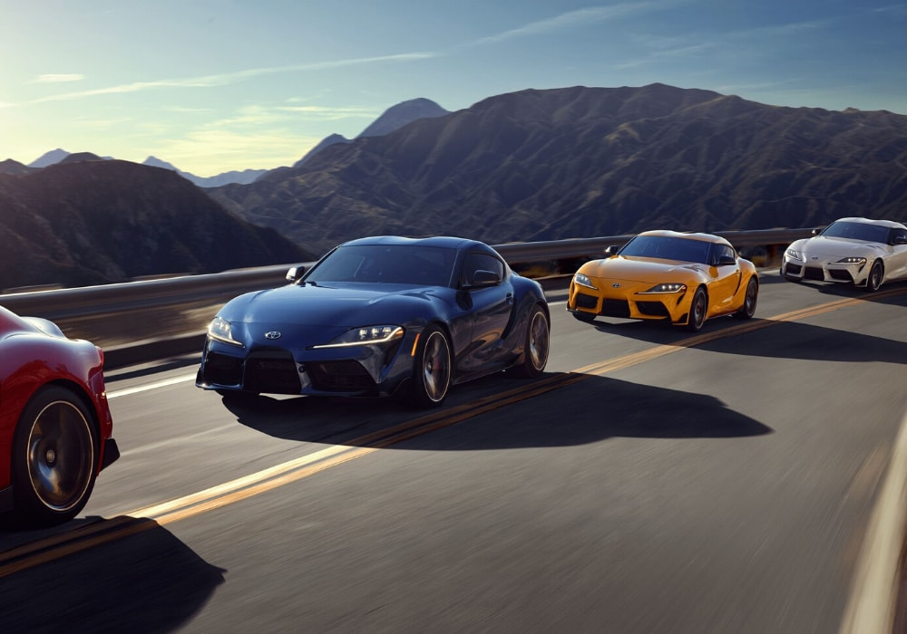 2020 Toyota Supra models in multiple different colors driving single file through mountainous roads