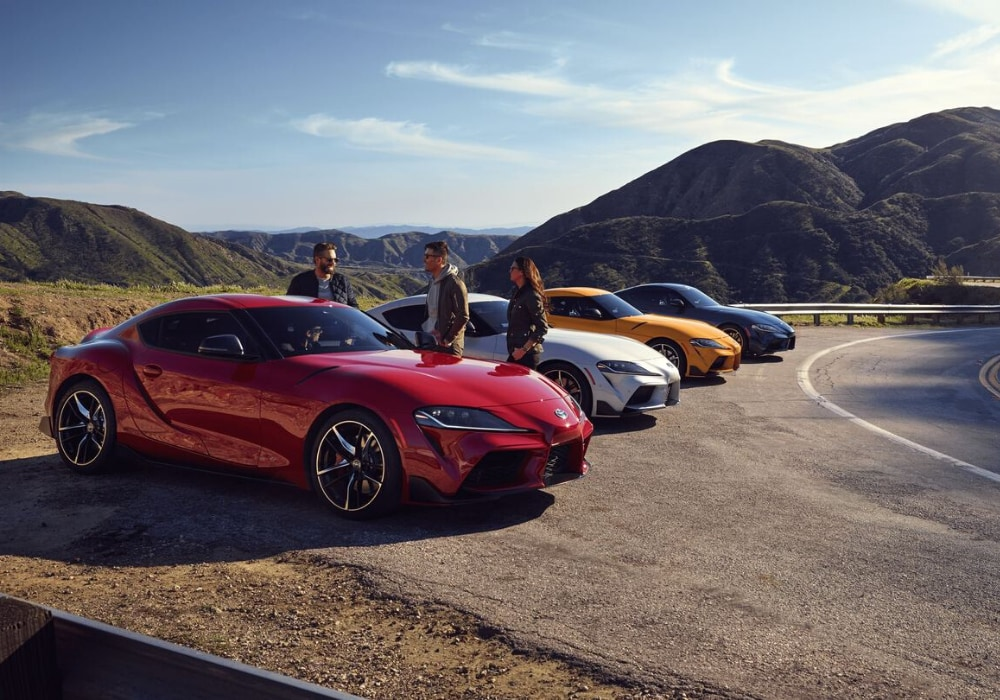 2020 Toyota Supra models of many different colors parked in a line off road mountain road cliff