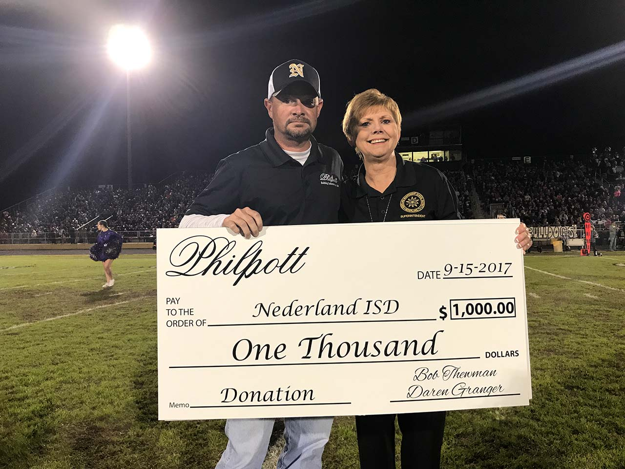 Philpott presents a check to Nederland ISD
