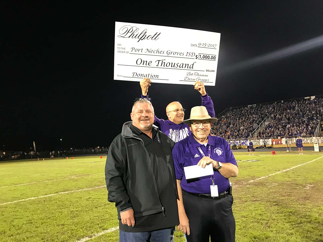 Philpott presents a check to Port Neches-Groves ISD