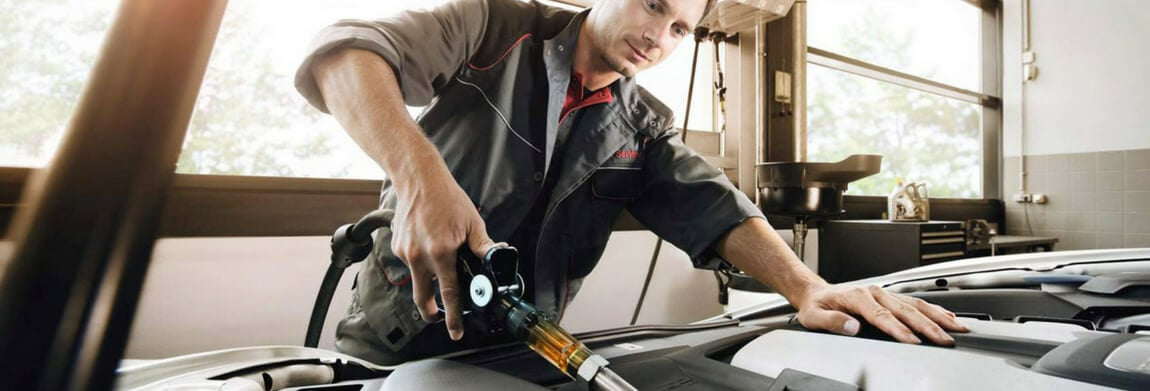 Porsche technician performing an oil change