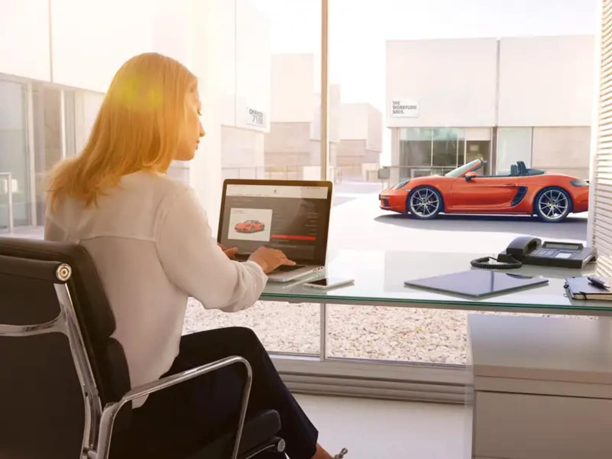 Lady viewing Porsche specials on her laptop